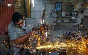 Carlos Diaz cutting metal to make a knife in his shop in Guatemala
