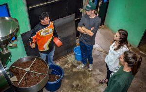 Nate Caverly (BA Accounting '19), Morgan Burns (BA Accounting '18), and Jaimee Beckett (BA Computer Science '19) learning to roast coffee with Victor Catavi in Guatemala