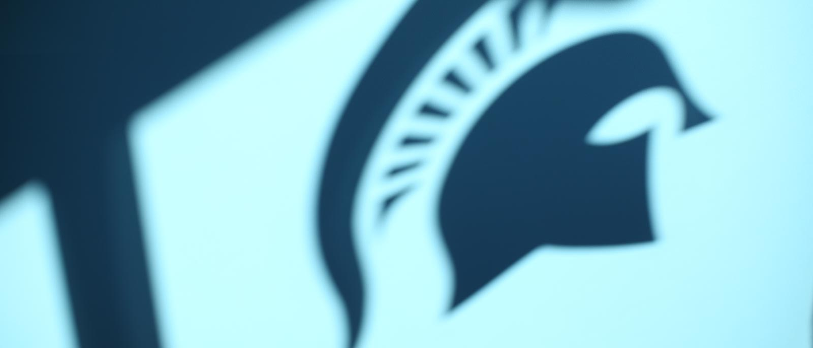 Silhouette of Spartan helmet logo against a lit wall