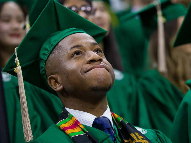 Graduating business school student at MSU looks up, hopeful, at undergraduate commencement ceremony.