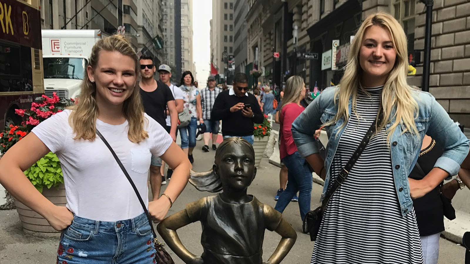 FMI scholars standing next to Fearless Girl sculpture on Wall Street.