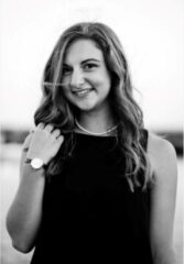 Black and white photo of Amanda Neumann, smiling, in a black dress.