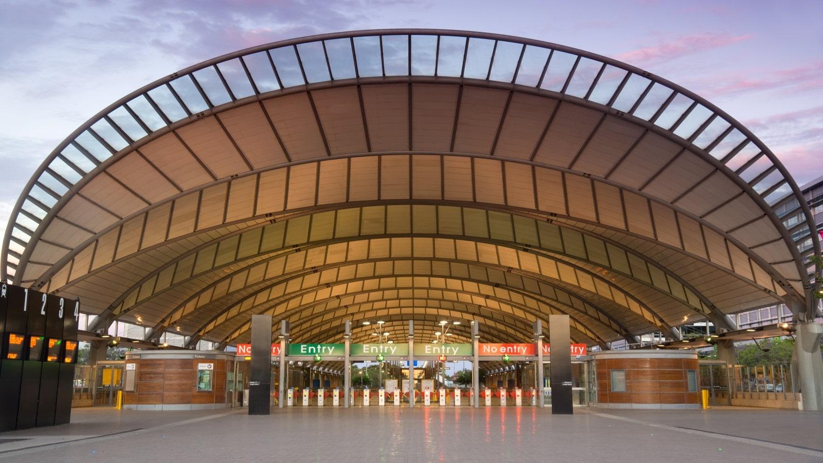 The modern train station at Sydney Olympic Park, seen at dusk under a colourful sky.