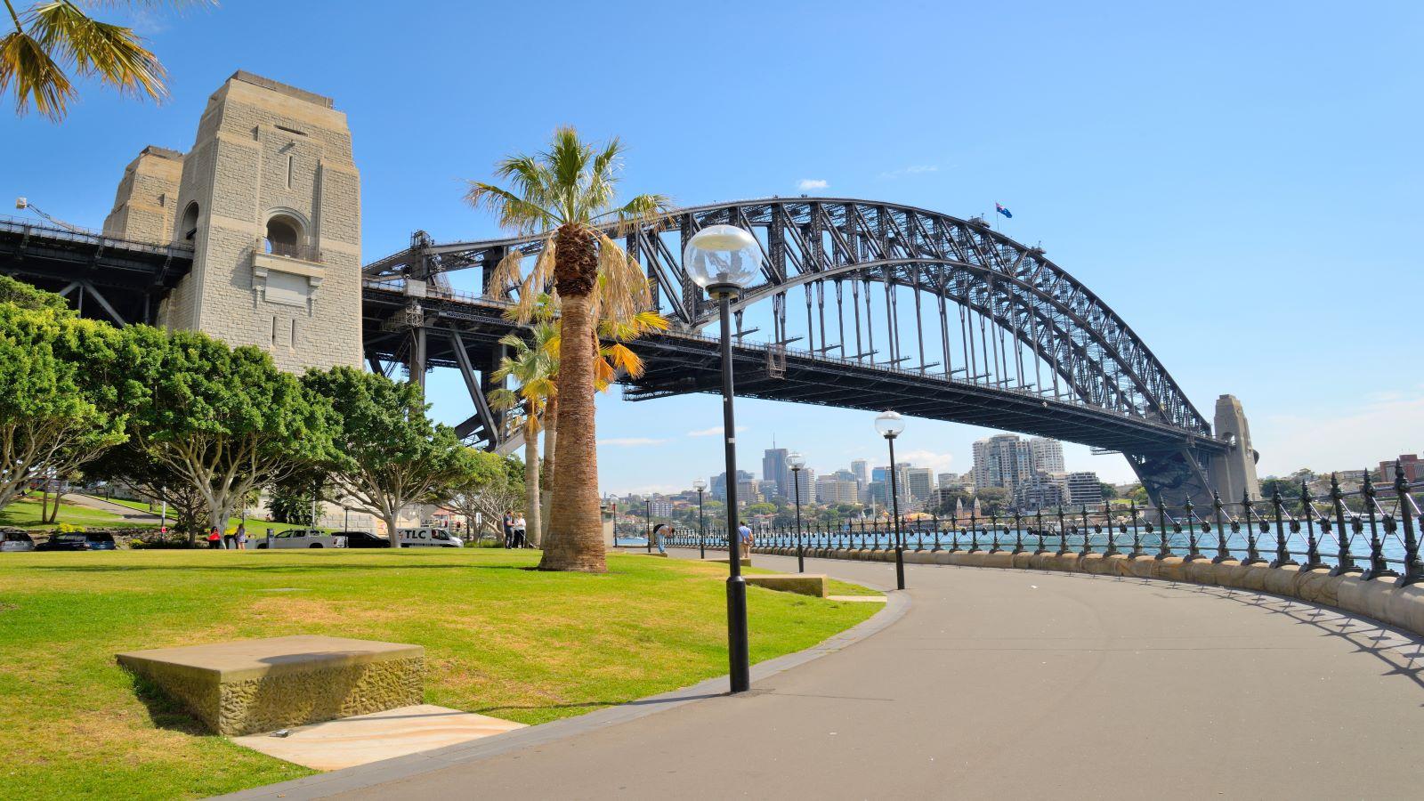 Side view of Sydney Harbour bridge in bright blue sky.