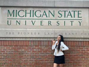 Simone Nagi posing in front of a Michigan State University sign