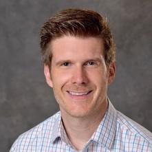 Headshot of a man wearing a plaid shirt